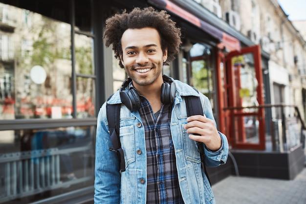 Bonito elegante afro-americano com penteado afro, vestindo casaco jeans e fones de ouvido, andando pela cidade.