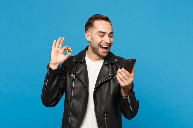 Bonito elegante jovem com a barba por fazer em t-shirt branca de jaqueta preta segura na mão celular bitcoin moeda isolada no retrato de estúdio de fundo de parede azul. conceito de estilo de vida de pessoas. simule o espaço da cópia