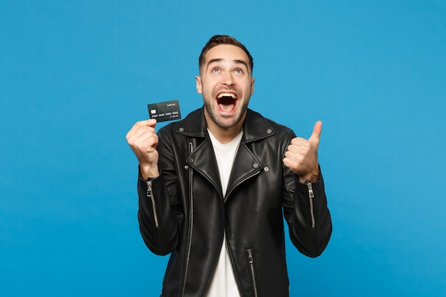 Bonito elegante jovem com a barba por fazer em uma jaqueta de couro preta t-shirt branca segura na mão cartão de crédito isolado no retrato de estúdio de fundo de parede azul. conceito de estilo de vida de pessoas. simule o espaço da cópia.