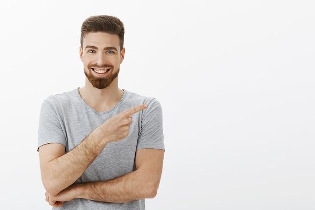 Bonito empreendedor independente charmoso com barba e penteado descolado em camiseta cinza apontando para o espaço da cópia e sorrindo com segurança e contente contando às pessoas sobre um ótimo produto