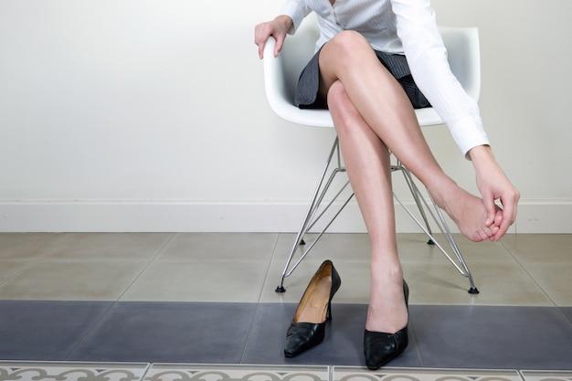 Bonito empresária sentado em uma cadeira massageando seu pé