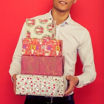 Bonito empresário asiático segurando uma caixa de presente sobre fundo vermelho