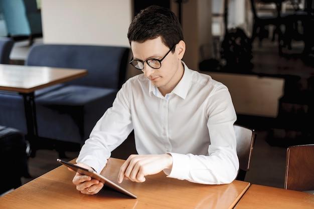Bonito empresário caucasiano operando em um tablet enquanto está sentado em uma mesa, usando óculos e vestido com uma camisa branca.