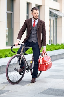 Bonito empresário com uma jaqueta com bolsa vermelha, sentado em sua bicicleta nas ruas da cidade.