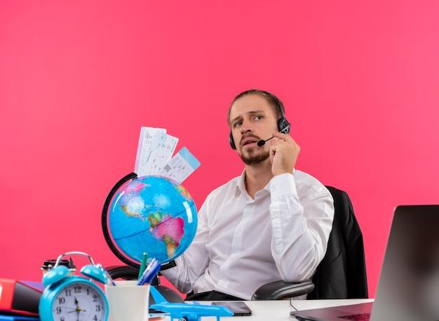 Bonito empresário de camisa branca e fones de ouvido com um microfone segurando passagens aéreas, ouvindo um cliente com cara séria sentado à mesa em escritório sobre fundo rosa