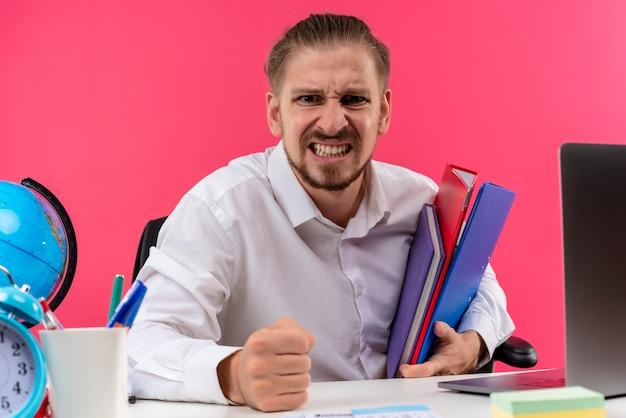 Bonito empresário de camisa branca segurando pastas, olhando para a câmera com cara de zangado, sentado à mesa em escritório sobre fundo rosa