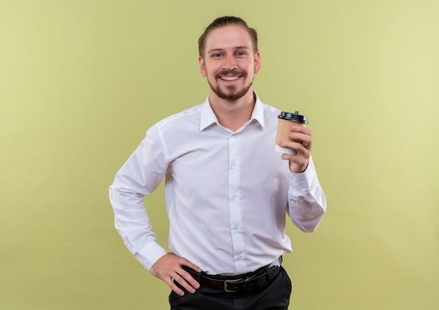 Bonito empresário de camisa branca segurando uma xícara de café olhando para a câmera e sorrindo alegremente em pé sobre um fundo verde-oliva
