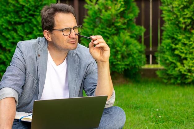 Bonito empresário de meia-idade sentado ao ar livre na grama com um laptop segurando um lápis, pensando pensativamente em conceitos de negócios iniciais, ideias de inicialização, cursos de autodesenvolvimento, conceito de inspiração