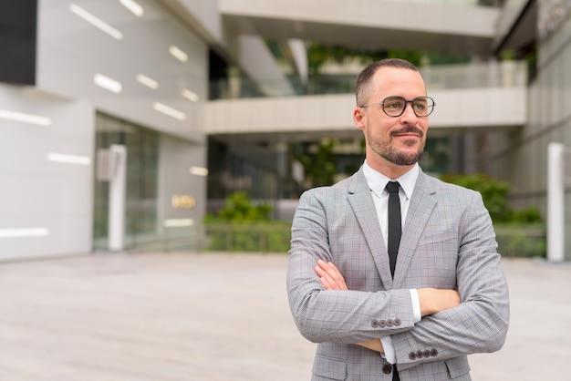 Bonito empresário hispânico careca e barbudo pensando com os braços cruzados na cidade
