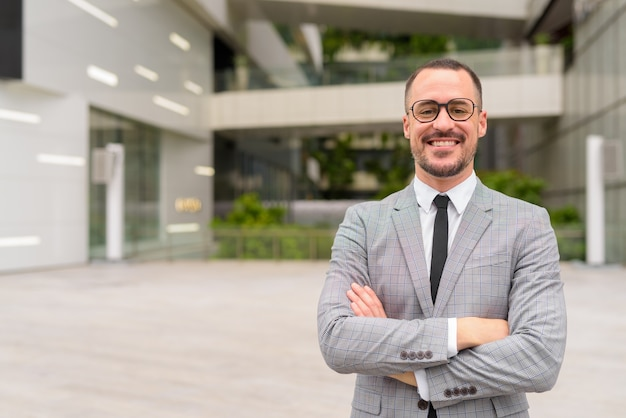 Bonito empresário hispânico careca e barbudo sorrindo com os braços cruzados ao ar livre da cidade
