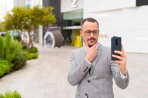 Bonito empresário hispânico careca e barbudo tirando uma selfie na cidade ao ar livre