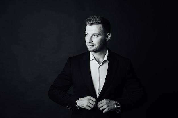 Bonito empresário masculino com terno posando em um estúdio fotográfico. h