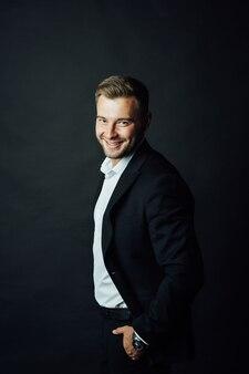 Bonito empresário masculino com terno posando em um estúdio fotográfico.