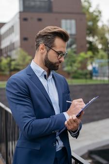 Bonito empresário pensativo segurando a prancheta, escrevendo, analisando o projeto de planejamento de documentos