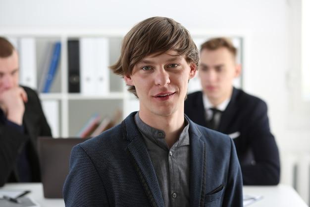 Bonito empresário sorridente em retrato de terno no local de trabalho, olhando diretamente