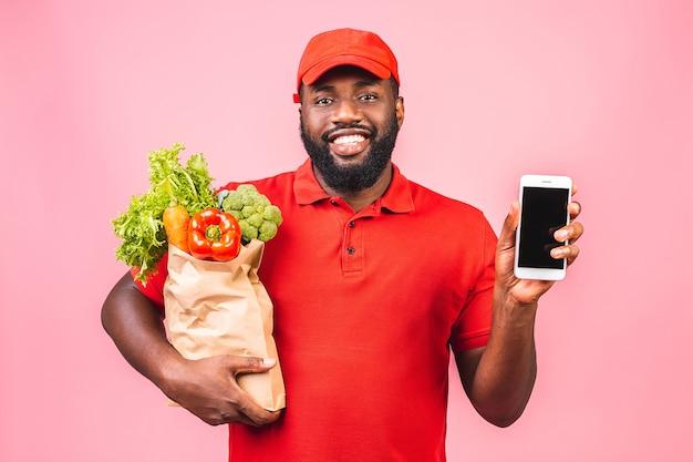 Bonito entregador afro-americano carregando uma caixa de comida de supermercado da loja