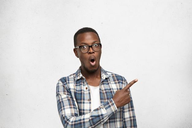 Bonito, espantado e surpreso jovem estudante de pele escura ou cliente de óculos e camisa quadriculada, apontando o dedo indicador