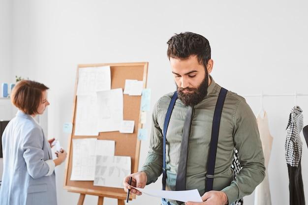 Bonito estilista masculino verificando planos para a linha de roupas no ateliê