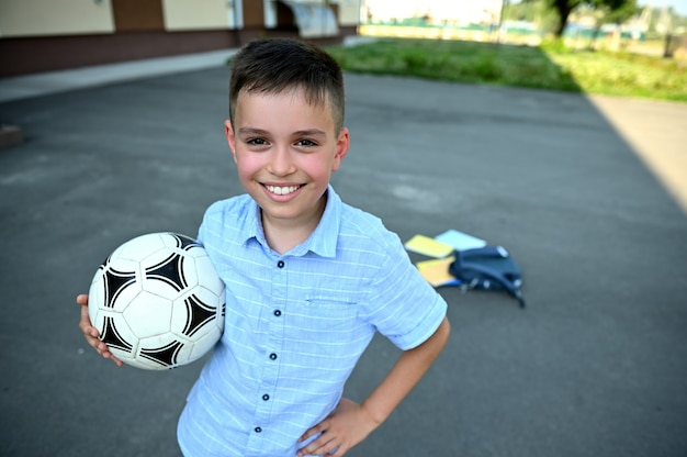 Bonito estudante alegre com uma bola de futebol nas mãos, sorrindo com um sorriso no fundo da mochila espalhada com material escolar no pátio da escola. lazer. descanse entre as aulas