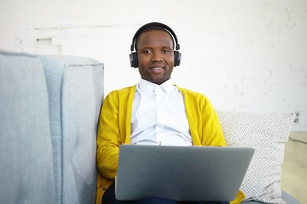 Bonito estudante preto do sexo masculino vestindo casaquinho amarelo sobre camisa branca, estudando em casa, usando laptop e fones de ouvido, ouvindo palestra online. homem feliz curtindo música pelo fone de ouvido no sofá