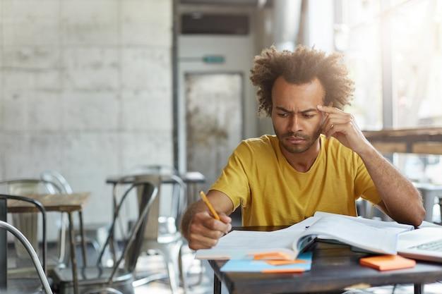Bonito estudante sério de pele escura vestindo camiseta amarela, fazendo anotações com lápis enquanto está sentado à mesa do café com o computador laptop e livros didáticos, fazendo pesquisas