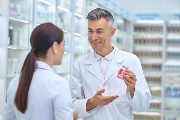 Bonito farmacêutico de cabelos grisalhos e sorridente, mostrando um frasco de medicamento para sua colega de cabelos escuros