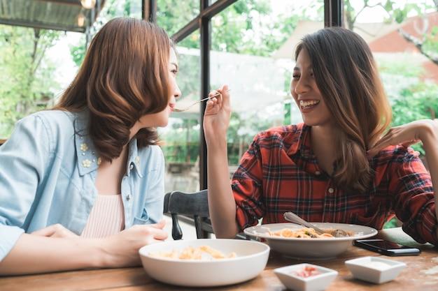 Bonito, feliz, mulheres asian, lésbica, lgbt, par, sentando, cada lado, comer, um, prato, italiano, marisco