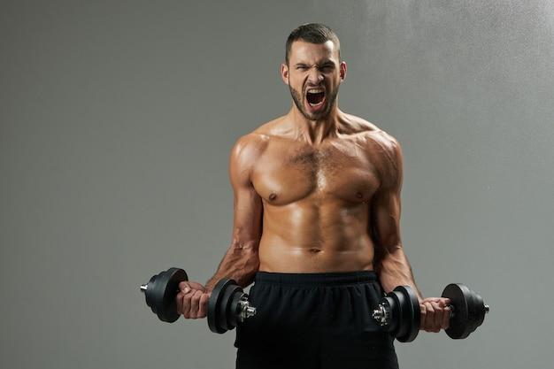 Bonito fisiculturista saído com um torso poderoso desenvolvendo músculos com halteres em salas internas