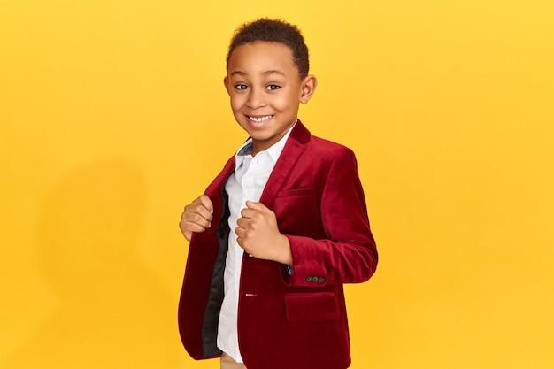 Bonito fofo afro-americano pequeno fashionmonger posando isolado tendo uma expressão facial confiante, sorrindo, ajustando a jaqueta de veludo carmesim da moda.