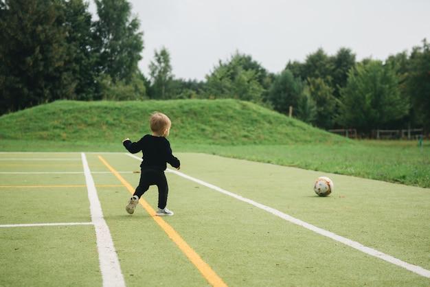 Bonito garoto de um ano de idade jogando futebol com uma bola na grama artificial