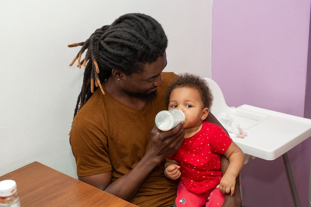 Bonito homem africano com dreadlocks alimentando sua filha com uma garrafa