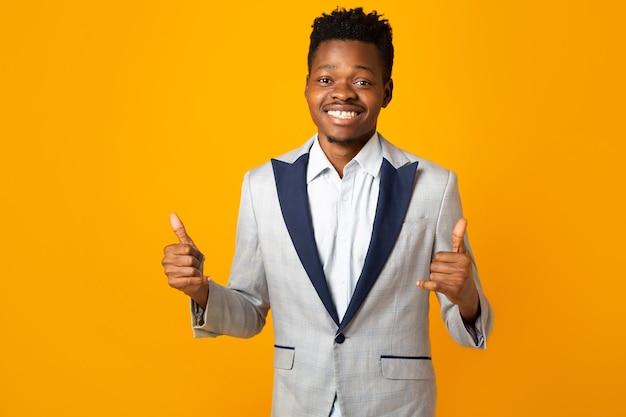 Bonito homem africano com uma jaqueta em fundo amarelo com gesto de mão