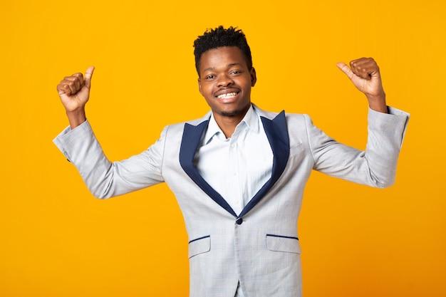 Bonito homem africano com uma jaqueta em um fundo amarelo com as mãos para cima