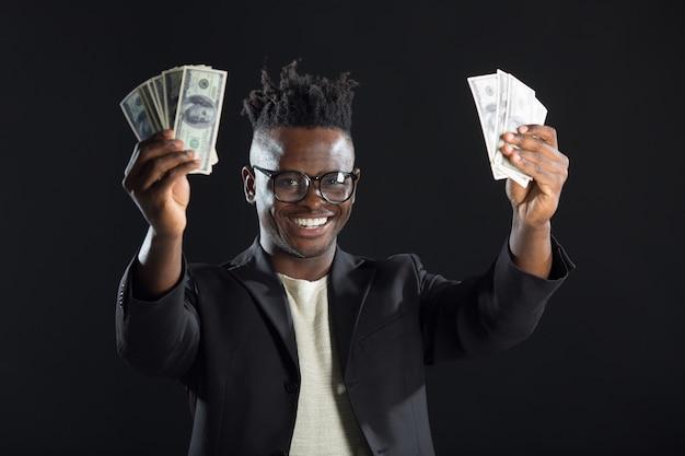 Bonito homem africano de terno e dólares nas mãos