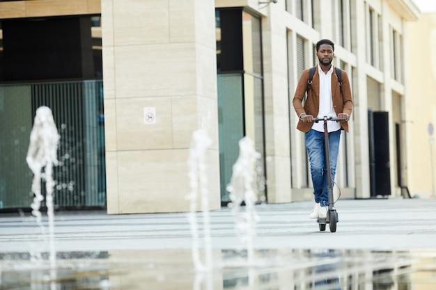 Bonito homem africano montando scooter elétrico na cidade