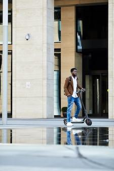 Bonito homem africano montando scooter elétrico