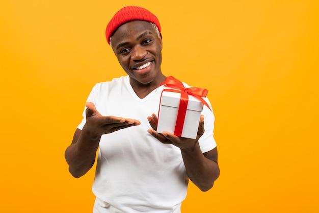 Bonito homem africano negro com um sorriso em uma camiseta branca mantém uma caixa um presente com uma fita vermelha para um aniversário em um amarelo com espaço de cópia