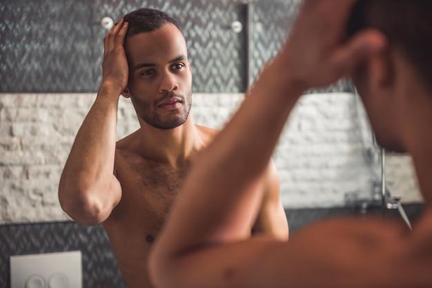 Bonito homem afro-americano nu está examinando seu rosto