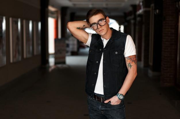 Bonito homem americano com óculos vintage e colete jeans com uma camiseta branca na rua