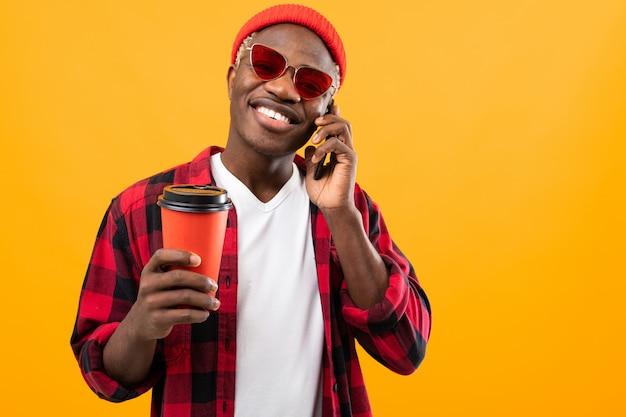 Bonito homem americano negro falando ao telefone enquanto segura um copo de café para viagem no estúdio amarelo