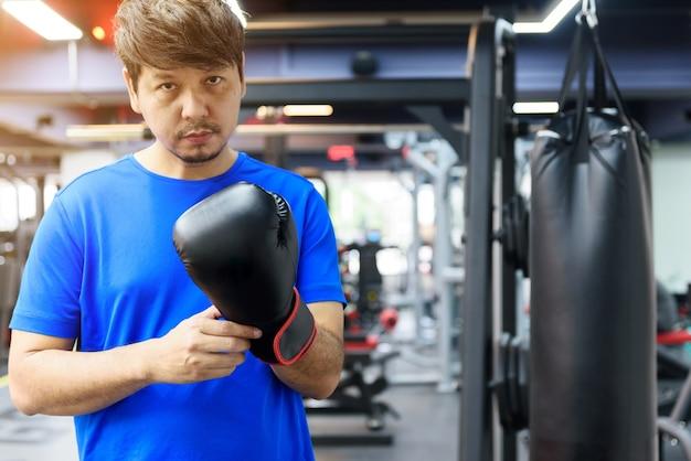 Bonito homem asiático com barba usa uma camisa esporte azul com luvas de boxe pretas no ginásio olha para a câmera, o esporte e o conceito de treino
