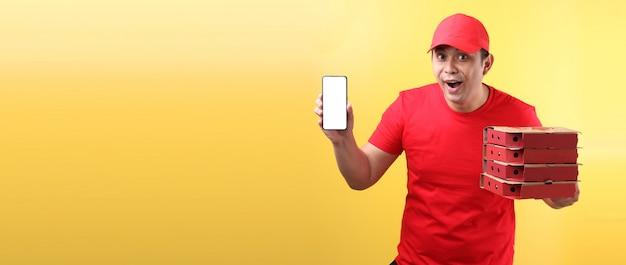 Bonito homem asiático de boné vermelho, dando comida italiana pizza em caixas de papelão isolado segurando o telefone móvel com tela vazia branca em branco.