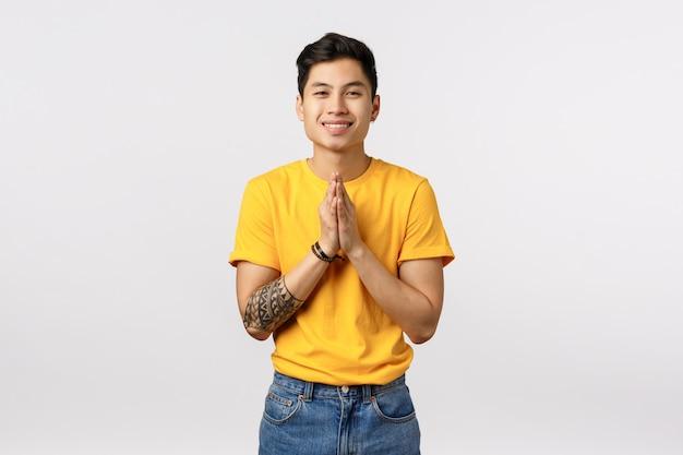 Bonito homem asiático de camiseta amarela em rezar gesto