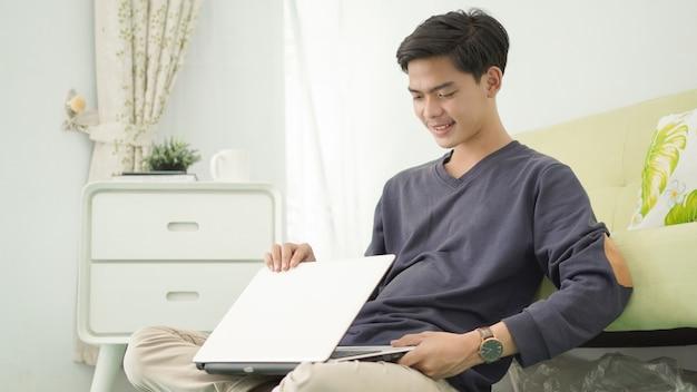 Bonito homem asiático desligando o laptop depois de trabalhar em casa