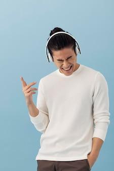 Bonito homem asiático ouvindo música com fones de ouvido