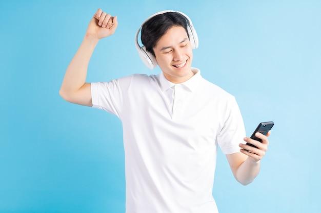 Bonito homem asiático ouvindo música e dançando