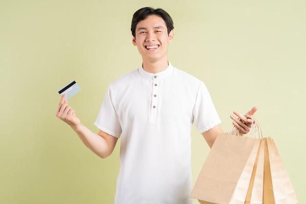 Bonito homem asiático segurando um cartão de crédito e carregando sacolas de compras