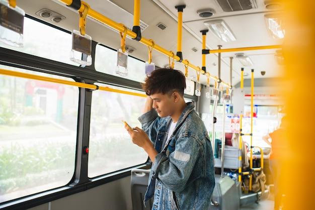Bonito homem asiático sentado no ônibus da cidade e digitando uma mensagem no telefone.