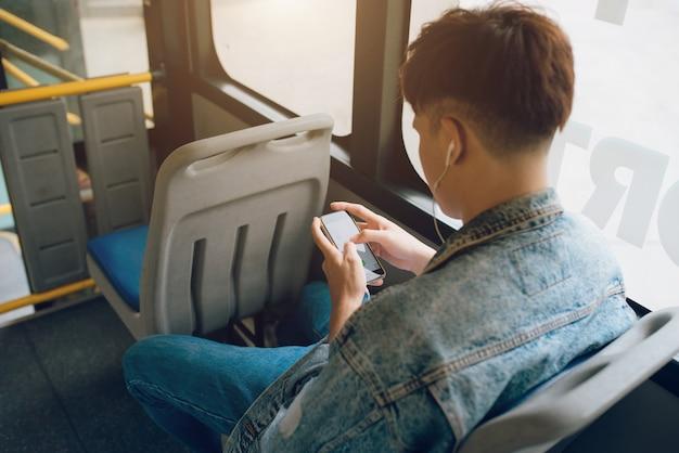 Bonito homem asiático sentado no ônibus da cidade e enviando mensagem no telefone.