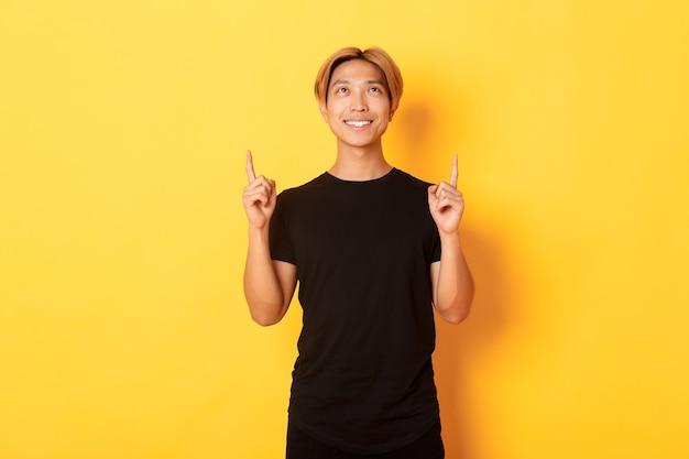 Bonito homem asiático sorridente em t-shirt preta apontando os dedos para cima, parede amarela.